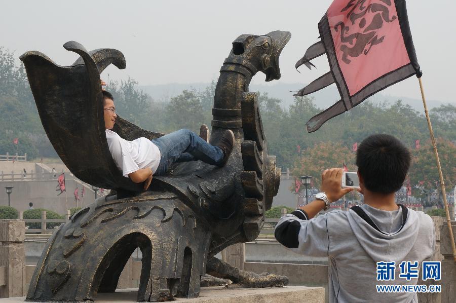 河南省焦作市影视城,一名游客躺在景观雕塑上拍照留影.