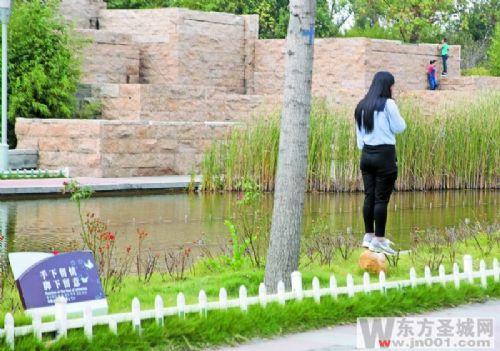 一位游客不仅随意践踏草坪还双脚踩在景区的音箱上